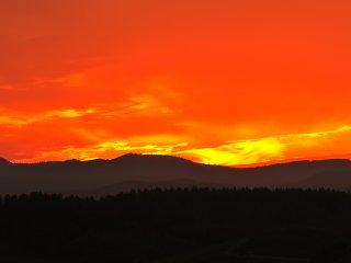 Lors du coucher de soleil, émerveillés, les spectateurs restent bouche bée devant le rouge flamboyant du ciel