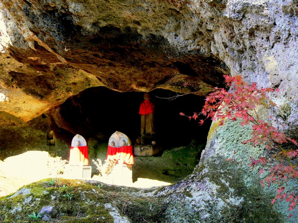 Statues with red aprons in the entrance to one of the caves