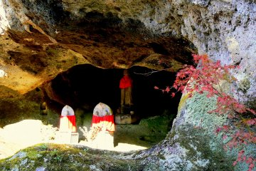<p>Statues with red aprons in the entrance to one of the caves</p>