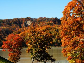 Autumn foliage at its peak in late October on the shore of Lake Kanayama in Minamifurano