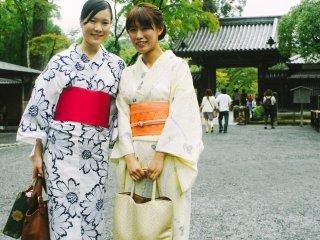 Dua pengunjung yang mengenakan pakaian tradisional (yukata dan kimono) di depan pintu masuk Kinkaku-ji