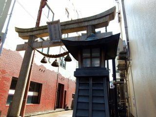 The main gate of Shibata Shrine stands on a narrow, old, shopping street