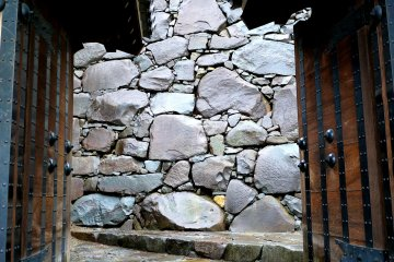 <p>Stone walls framed by a gate</p>