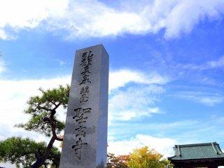 青空の下聳え立つ、聖玄寺の石柱