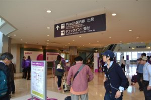 Purple-clad staff are stationed near the self-check-in kiosks to help confused passengers
