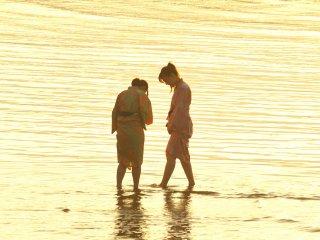 浴衣姿の少女二人、渚で戯れる姿が微笑ましい