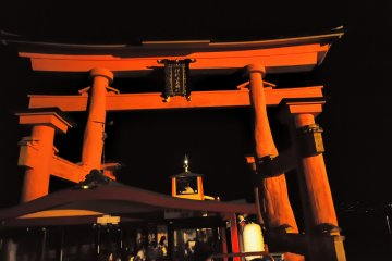<p>My boat passing through the torii gate which towers over it as we get closer</p>