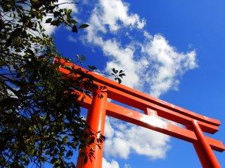 Gerbang torii merah pertama menjulang tinggi ke langit biru. Dari sini, Anda harus menaiki banyak tangga batu untuk mencapai kuil.
