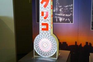 ป้ายไฟกูลิโกะรุ่นแรกสุดซึ่งมีรูปร่างคล้ายปรอทขนาดใหญ่ที่มีสัญลักษณ์กูลิโกะแมนอยู่ด้านบน มีความสูง 33 เมตร โดยป้ายนี้ถูกติดตั้งครั้งแรกที่โดตนโบริเมื่อปี ค.ศ.1935