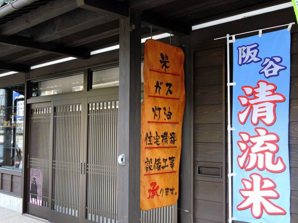 伝統的日本家屋の店先には「米・ガス・灯油・住宅機器・設備工事」と書いてある・・・まるでよろず屋だ!