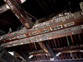 Giấy dán hành hương ở trên dầm gỗ của cánh cổng