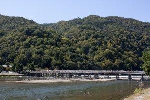 อีกมุมหนึ่งของสะพานโทเก็ตซึเคียว (Togetsukyo Bridge) หรือฉายาสากลว่า Moon Crossing Bridge ที่สะพานดั้งเดิมนั้นสร้างขึ้นตั้งแต่สมัยเฮอัน (Heian Period) ในยุคก่อตั้งกรุงเกียวโต และนี่ก็คือมุมอันงดงามที่ได้รับการขึ้นทะเบียนให้เป็นสถานที่ท่องเที่ยวทางประวัติศาสตร์แห่งญี่ปุ่น (Nationally-designated Historic Site) ใน Cultural Properties of Japan หมวดของ Place of Scenic Beauty ที่ดูแลโดยกระทรวงวัฒนธรรมญี่ปุ่น