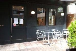 ด้านหน้าร้านLe Petit Mac - Oike (ル・プチメック 御池) ที่มีมุมนั่งชิลล์สบายๆ กับร้านเท่ๆ ในโทนสีดำ