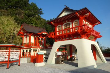 <p>The shrines colors are a stark contrast to the colors of the sea and sky</p>