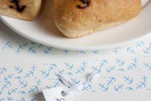 บรรดาขนมปังอบที่มีการทำสัญลักษณ์สมอเรือซึ่งเป็นโลโก้ของร้านด้วยลงบนขนมปังอย่างมีเอกลักษณ์
