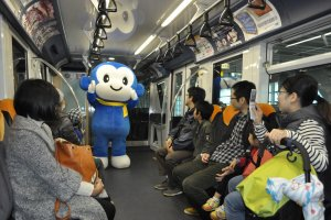 Maskot Kota Chiba menghibur penumpang yang berkunjung ke bengkel monorail.