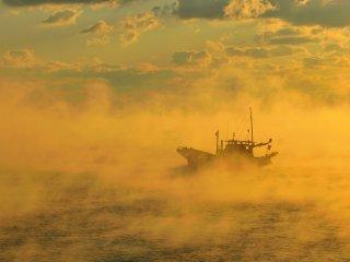 船が霧の上を滑るように移動する