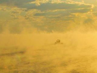 雲海のような中から漁船が見え隠れする