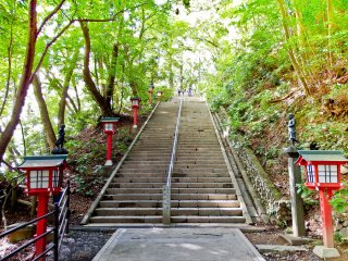 The final staircase leading up to Yakuo-in Temple where you will notice many red lanterns and several black statues representing some of Takao`s many Guardian Deities