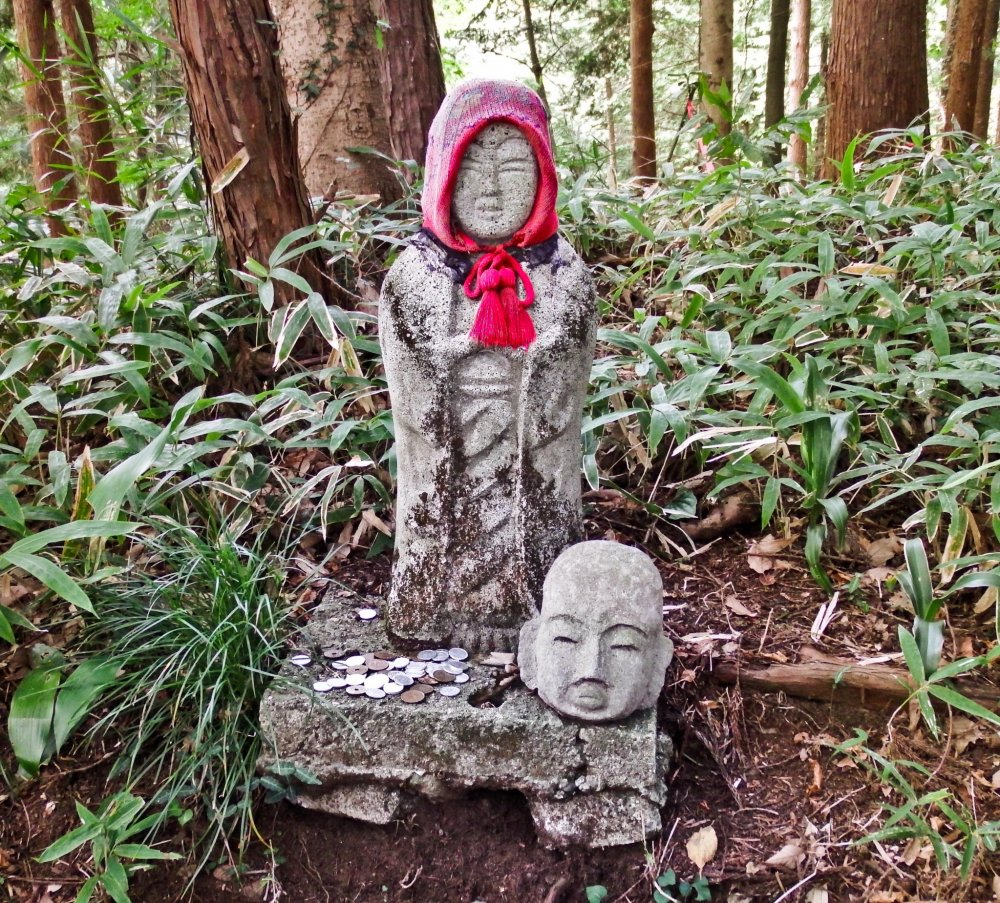 Several minutes further down this path was another eerie Jizo. This time it had a decapitated head placed next to it