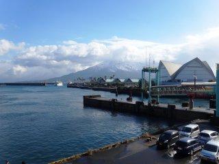 Sakurajima cubierto en una rara nevada, como se ve desde el puerto de Kagoshima