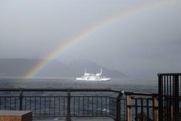 <p>El clima h&uacute;mero produce un arcoiris sobre el ferri que corre hacia Sakurajima</p>