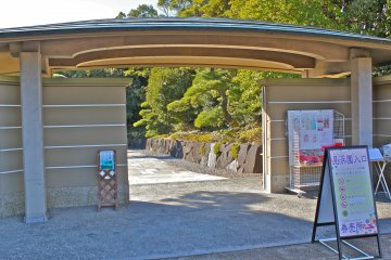 <p>The entrance gate at Mihama-en&nbsp;has a large copper-shingled roof. The four, white parallel lines indicate ranking within the Japanese gardens across the country.</p>