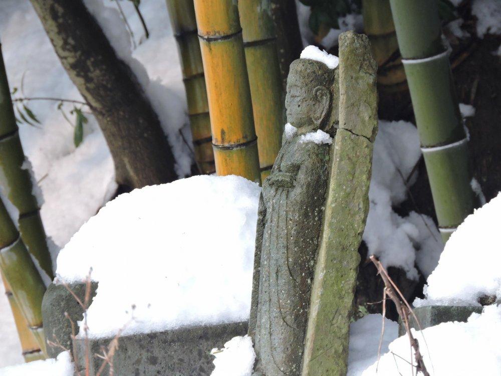 눈 덮인 지조 묘지에 고독하게 서 있는 부서진 지조상
