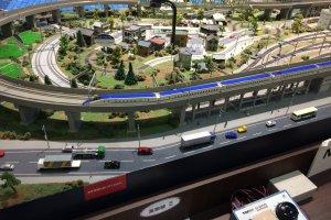 ミニチュアスケールの新幹線でも走り去る姿は迫力がある。写真は、最新のE7系新幹線。道路や街並みなど、ジオラマの背景も、細部まで緻密に作りこまれている。