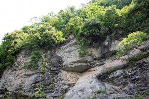 岩畳の対岸にある「秩父赤壁」。500mに渡り、圧倒的な存在感を誇る絶壁だ。中国揚子江の景勝地「赤壁」にちなんで命名。名のとおり、部分的に岩が赤く色づいている。壁に流れ落ちる明神の滝も見られる。