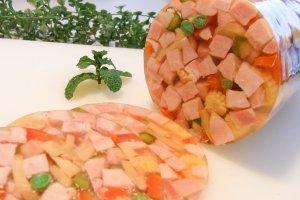 シンケンアスピック、別名「ハムと野菜のゼリー寄せ」。角切りにしたハム、ピクルス、パプリカなどを酸味をきかせたゼラチンで固めたもの。宝石箱のような華やかさが、おもてなしの食卓を彩る。