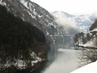 川沿いの道路から集落に降りて行く 遠景の山に霧が立ち上っていく