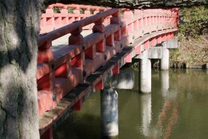A red Japanese bridge inside the park