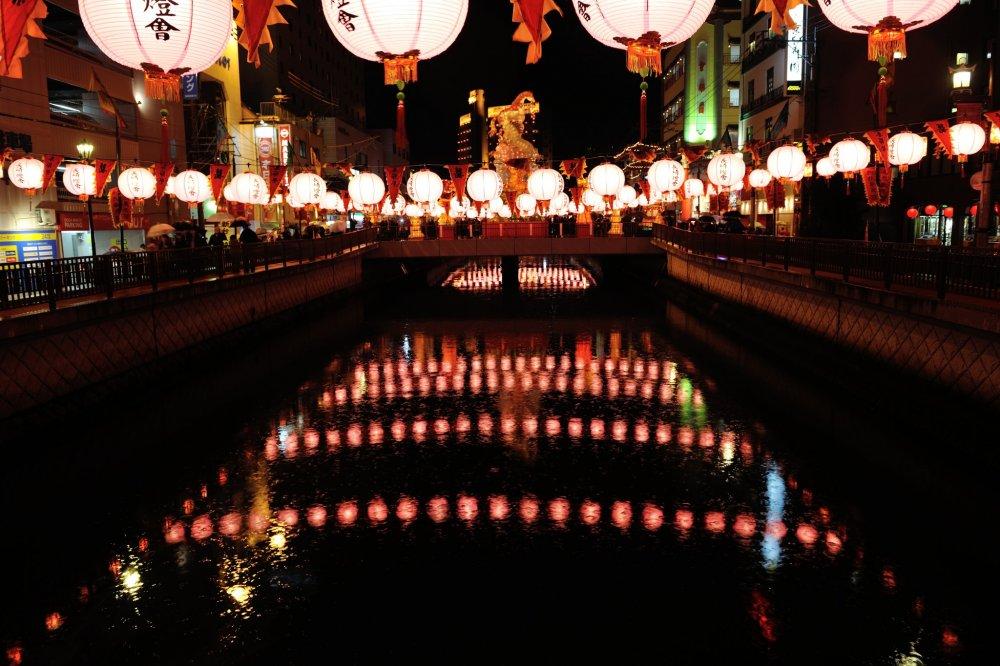 Des lanternes illuminées se reflètent dans la rivière Doza
