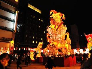 Люди на ведущем в Чайна-таун мосту Синти любуются гигантскими световыми статуями