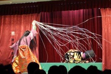 <p>He throws a net at the praying shogun</p>