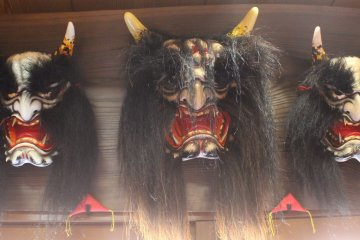 <p>Masks hung up above the doorway. The masks get larger as the play goes on</p>