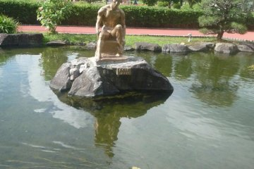 Pond with statue and several gold koi fish.