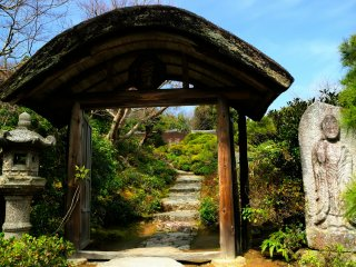 屋根にはアーチ型の桧皮葺!石灯篭と石仏を左右に配す、とても凝った山門だ