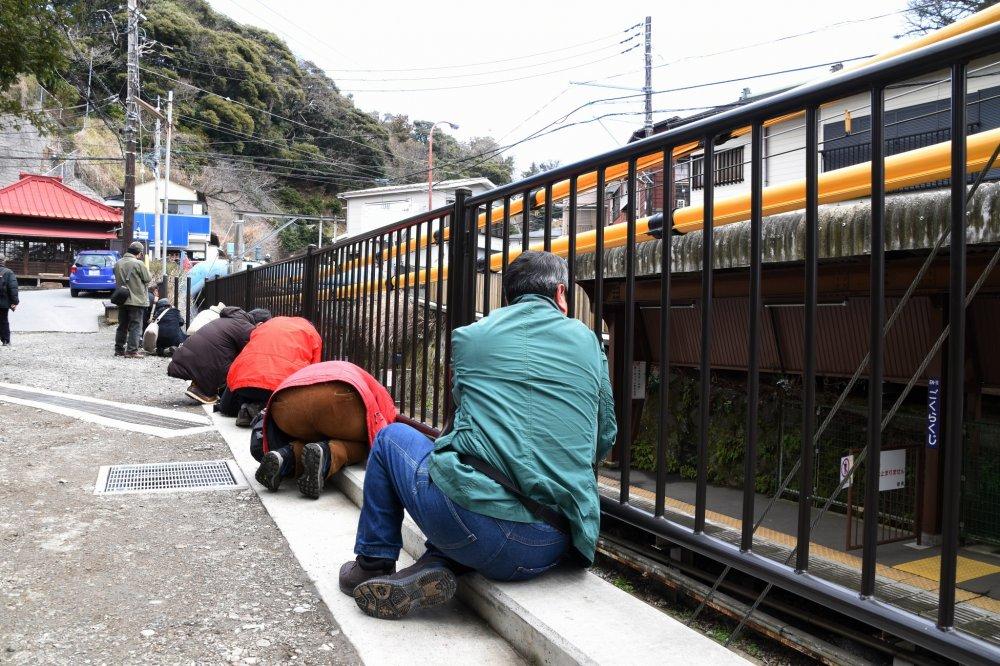 ช่างภาพนั่งเรียงรายกันริมรั้วเหล็กของสถานีโงะคุระคุจิของรถไฟสายเอะโนะเด็น