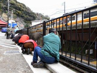 江ノ電極楽寺駅近くの鉄柵に貼り付く写真家たち