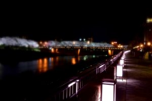 Mysterious view of the illuminated Sakura Bridge and the riverbank pathway of Asuwa River in Fukui