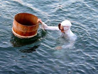 Seorang Ama menjejakkan diri di dalam air sembari berpegangan kepada bak kayu
