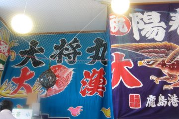 The large 'big catch' flags from various harbors drape the walls