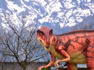 หุ่นไดโนเสาร์ยืนอยู่ตรงเชิงสะพานคัตซึตยะมะ พร้อมกับฉากหลังของภูเขาหิมะ