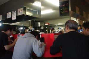 カウンター席のみ。奥の厨房は広々としており、女性2名男性2名のスタッフが働いています。