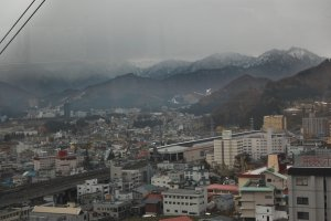 Pemandangan kota Yuzawa dari atas. Terlihat mendung dengan pegunungan bersalju di sekelilingnya.
