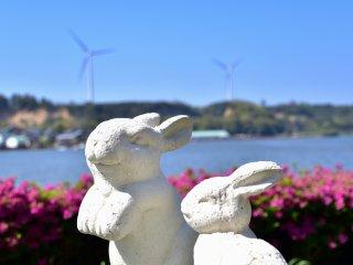 レイクサイド北潟湖畔荘庭園のウサギの石像。ツツジと美しい湖、風車に囲まれて幸せそうだ。