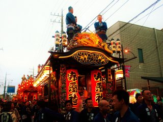 A large group of team members help pull the yatai to the battle area.