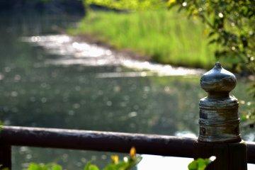뒤에서 빛나는 연못을 가진 청동 마개교 기둥